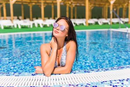 Beautiful woman relaxing in the swimming pool Stock Photo