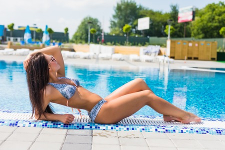Beautiful sexy luxurious girl lies on the edge of the swimming pool, sunbathing, tanned perfect body, long hair, trend accessories, fashionable bright bikini relaxing on a tropical island, a top view Stock Photo