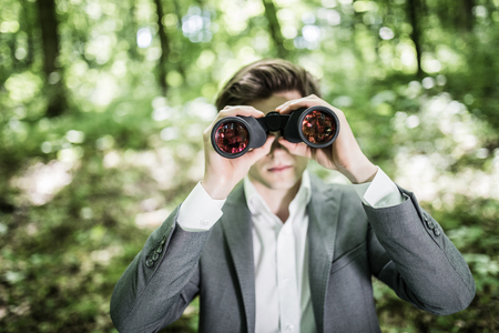 using binoculars: Tilt up image of young businessman using binoculars. Male executive is searching for opportunities. Professional is standing in office.