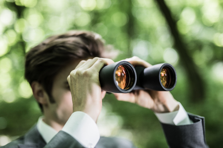 Business man in suit with binoculars looking at competitors on his market in green park. Freelancer executive is searching for opportunities in green park.