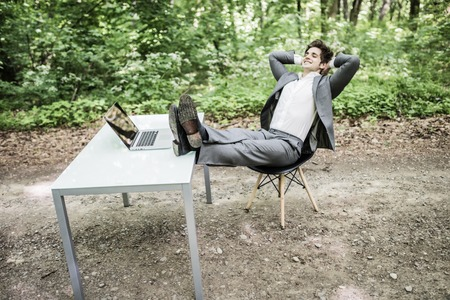 Relaxed business man in suit with heads over head and legs on office desk after successful work in green park. Freelancer relax after great deal in green forest.