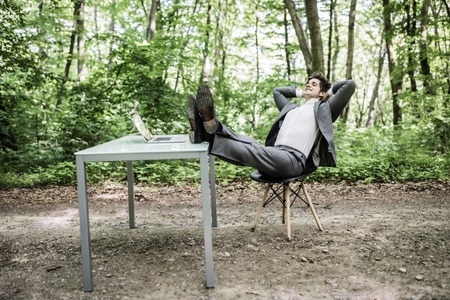 Relaxed business man in suit with heads over head and legs on office desk after successful work in green park. Freelancer relax after great deal in green forest. Business concept.