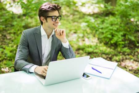 Young handsome business man working at laptop at office table in green park. Business concept.