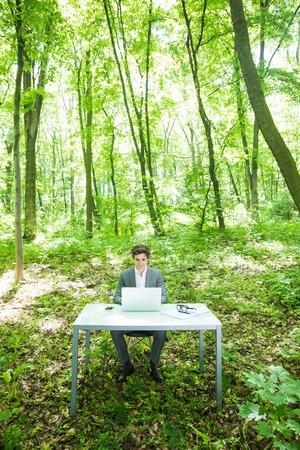 緑豊かな森林公園でのオフィスのテーブルにノート パソコンで作業のスーツで若いハンサムな実業家ビジネス コンセプトです。 写真素材