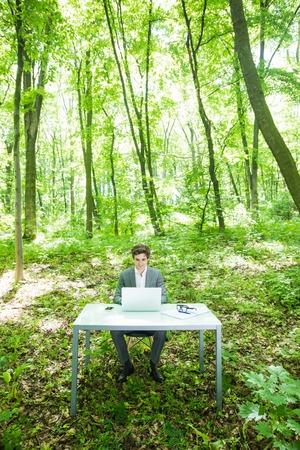 Young handsome business man in suit working at laptop at office table in green forest park. Business concept. Stockfoto