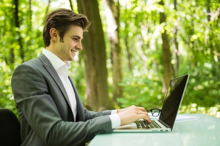 Portrait of handsome business man in suit at laptop at office table in green forest park. Business concept.