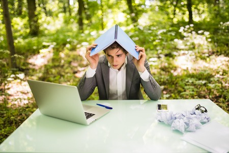 Young business man at work table office with laptop in green forest with notebook over head, too much work. Business concept Stock Photo