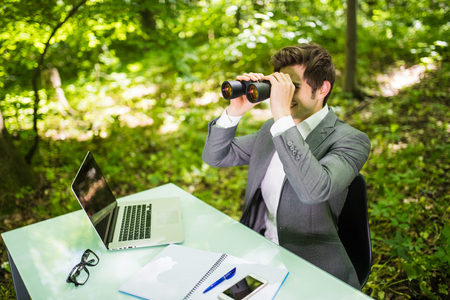 Young handsome business man at work table office with laptop in green forest with binocular looking for competitors. Business concept