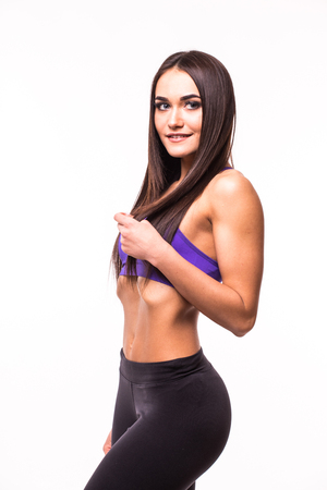 Portrait of a beautiful sports woman with hands on hips on white background