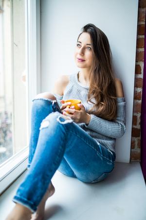 jong meisje dat van een ideale dag geniet die in de vensterbank zit. Een casual denimjeans en -blouse dragen, benen kruisen en door het raam kijken Stockfoto