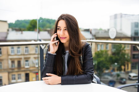 Portrait of beautiful young woman in coffee shop terrace, relaxing using smart phone, phone call conversation outdoors. Stock Photo