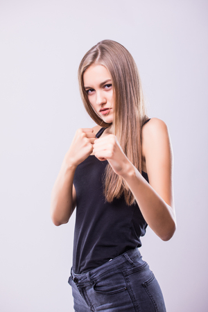 Portrait of young sport girl boxing against grey background.