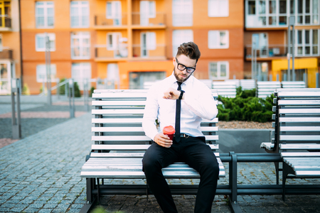 Young businessman is drinking coffee and resting from work in the street look at clock to be in time. Stock Photo