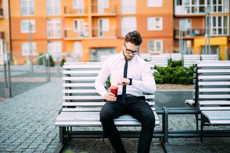 jeune homme d & # 39 ; affaires assis sur le banc en plein air et en regardant par-dessus le poignet de montre-bracelet
