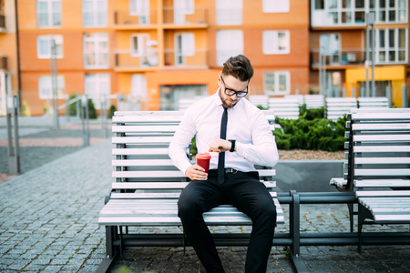 Young businessman sitting on the bench outdoors and looking on wrist watch