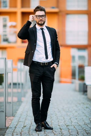 Handsome bearded businessman in classic suit is looking away while standing on the balcony of the office