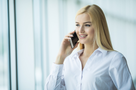 Image of smart business woman talking by mobile phone in office