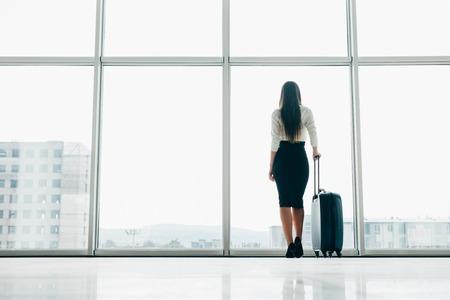 空港の窓で駐機場を見て、荷物で立って空港ラウンジで遅延飛行を待っている旅行者の実業家。出発前に搭乗ゲートにいる女性。旅行ライフスタイ