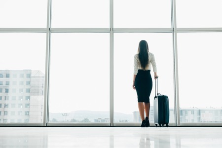 Traveler businesswoman waiting for delayed flight at airport lounge standing with luggage watching tarmac at airport window. Woman at boarding gate before departure. Travel lifestyle.