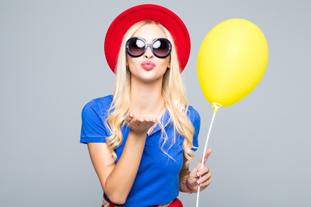 Pretty young woman in sunglasses with air balloon sends an air kiss over