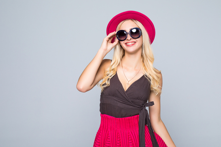winter fashion: Beautiful caucasian smiling hipster blonde woman model in bright colors stylish posing on gray background