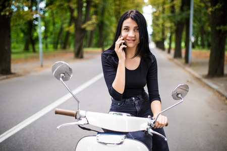 Young happy woman using mobile phone on moped Stock Photo