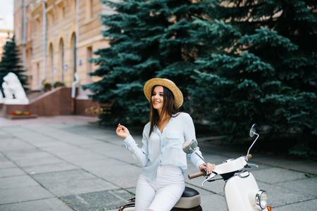Young beautiful woman sitting on a scooter outdoor