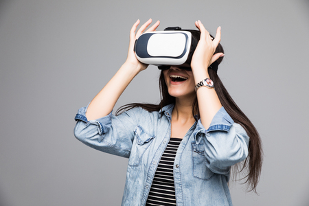 Smile happy woman getting experience using VR-headset glasses of virtual reality much gesticulating hands on gray background