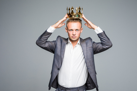 Business king. Confident businessman in crown standing isolated on gray background