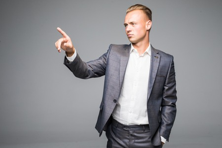 A young businessman pushes invisible button on a gray background Stock Photo