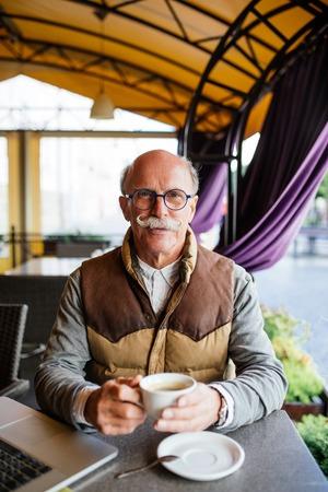 Elderly man having an espresso on a terrace