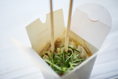 Noodles with pork and vegetables in take-out box on wooden table. Food.