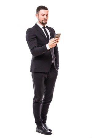 Young bearded business man typing message on smartphone touch screen.