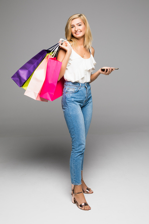 Beautiful shopping woman texting on her cell phone, isolated over white