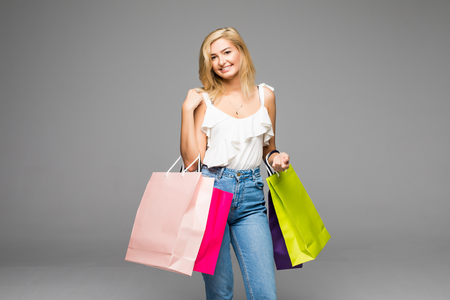 Portrait of young smiling woman with shopping bags, isolated over white background