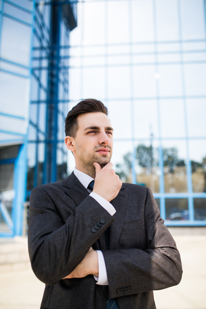 Confident thoughtful businessman in a suit holding hand on chin and looking away while standing outdoors with office building