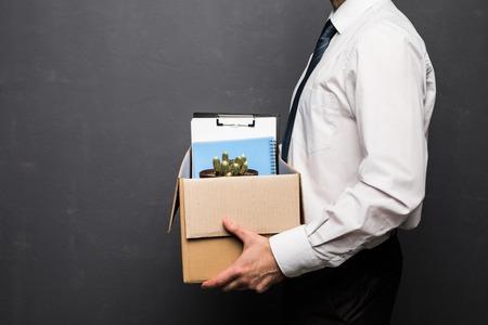 Abgefeuerter hübscher Geschäftsmann in der formellen Kleidung erhalten, der einen Kasten mit seinem Material, auf grauem Hintergrund hält