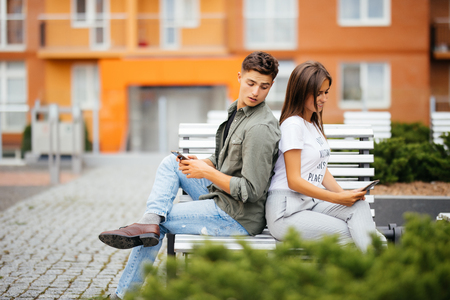 Young Caucasian couple on date, sitting back to back on park bench holding cellphones in hands, using app, making call, messaging or dialing number, spy at each other Stockfoto