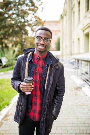 African man walking with to go coffee cup with copy space