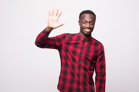 Positive human emotions, facial expressions, feelings, attitude and reaction. Friendly-looking polite young African American man waving his hand