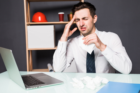 Sick businessman holding cup of hot tea and sneezing in tissue