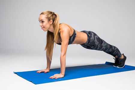 Young attractive woman practicing yoga, standing in Push ups or press ups exercise, Plank pose, working out, wearing sportswear bra and pants, full length, white loft studio background,
