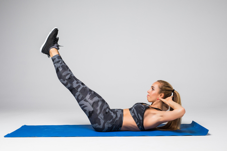 Healthy young blonde woman doing crunches wearing black top and shorts on grey background Banco de Imagens