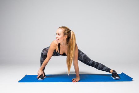 Side view portrait of beautiful young woman working out against grey wall, doing yoga or pilates exercise on gray background
