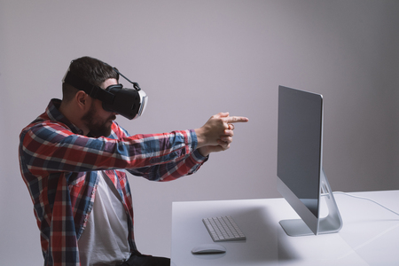 virtual reality simulator: Man in helmet virtual reality plays game. Man uses VR-headset display with headphones for virtual reality game in office. High-tech devices. Augmented reality device creating virtual space