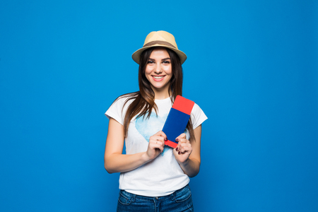 Woman traveler holding passport with ticket. Portrait of smiling happy girl on blue.