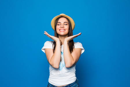 Close up portrait of a happy excited young woman in beach hat looking at camera isolated over blue background 免版税图像