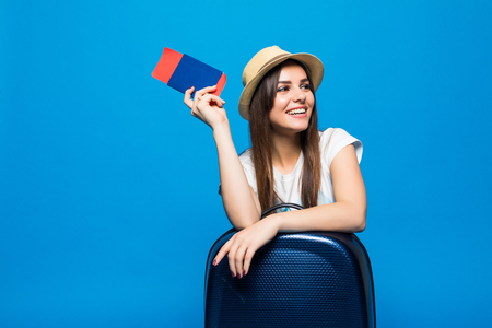 Portrait of trendy young female in wicker hat standing with suitcase and holding passport with tickets