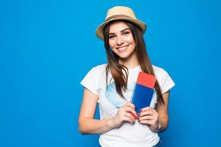 Portrait of a cute girl traveller in summer clothes showing passport with tickets to camera isolated over blue background