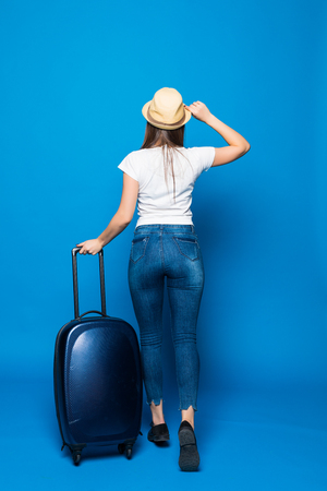 back view of walking woman with suitcase. beautiful girl in motion. backside view of traveler with baggage Isolated over blue background. traveling teen girl